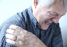 Shoulder joint pain in older man. Senior man suffering from pain in his shoulder stock photos