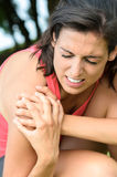 Shoulder lesion pain. Young woman grabbing her shoulder with an expression of pain because of an muscle sport injury Royalty Free Stock Photo