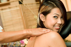 Shoulder Massage. A young attractive Asian woman having her shoulders massaged in a beauty salon Royalty Free Stock Image