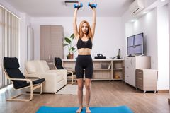 Shoulder military press workout during home training. Muscle gains royalty free stock photography