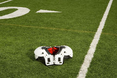 Shoulder pads on football field Stock Photography