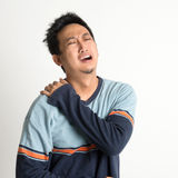 Shoulder pain. Asian man neck muscle sprain, or shoulder pain, on plain background stock photo