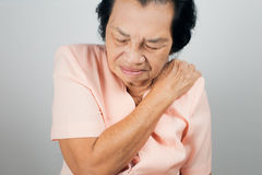 Shoulder Pain In An Elderly Person. On gray background Royalty Free Stock Photos
