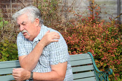 Shoulder pain or injury. An elderly man holding his shoulder because of injury or pain stock photography