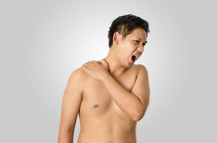 Shoulder pain. The man has shoulder pain isolated on gray background Stock Images