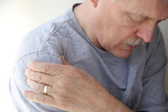 Shoulder pain in a senior man. Man suffering from aching shoulder stock photos