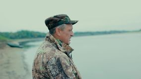 Portrait of a fisherman. Shoulder portrait of fisherman in profile on the river bank stock video footage