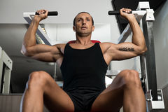 Shoulder Press Exercises. Fit man doing shoulder presses on a weight machine at the health club Royalty Free Stock Photo
