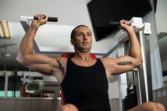 Shoulder Press Exercises. Fit man doing shoulder presses on a weight machine at the health club Stock Images