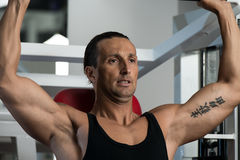 Shoulder Press Exercises. Fit man doing shoulder presses on a weight machine at the health club Royalty Free Stock Images