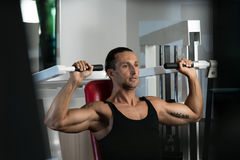 Shoulder Press Exercises. Fit man doing shoulder presses on a weight machine at the health club Stock Photos