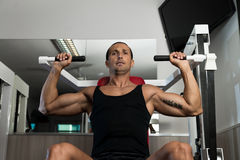 Shoulder Press Workout. Fit man doing shoulder presses on a weight machine at the health club Royalty Free Stock Image