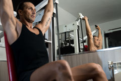 Shoulder Press Workout. Fit man doing shoulder presses on a weight machine at the health club Stock Photos