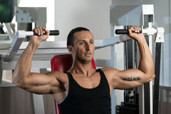 Shoulder Press Workout. Fit man doing shoulder presses on a weight machine at the health club Royalty Free Stock Photo