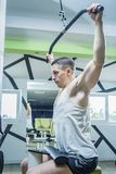Shoulder pull down exercise. Shoulder pull down machine. Fitness man working out lat pulldown training at gym. Upper body strength exercise for the upper back Stock Photo