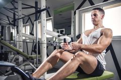 Shoulder pull down exercise. Shoulder pull down machine. Fitness man working out lat pulldown training at gym. Upper body strength exercise for the upper back Stock Photos
