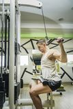 Shoulder pull down exercise. Shoulder pull down machine. Fitness man working out lat pulldown training at gym. Upper body strength exercise for the upper back Stock Photography