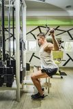 Shoulder pull down exercise. Shoulder pull down machine. Fitness man working out lat pulldown training at gym. Upper body strength exercise for the upper back Royalty Free Stock Photography
