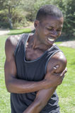 Shoulder sports injury. Lean muscular African American man in black tank top in park holds deltoid muscle afflicted by painful injury with agonized expression on Stock Photography