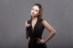 Shoulder turned to camera, sexy beautiful brunette with long natural hair make up, in black sleeveless costume suit Stock Photography