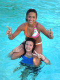 On Shoulders. A picture of two young teen girls in the swimming pool and one sitting on her shoulders Stock Image