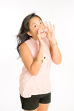 Shout Out Loud. Young woman calling out loud and cheerfully, cupping her mouth with her hands Royalty Free Stock Photography
