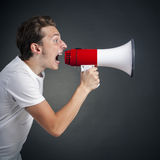 Shout. Young man shouting into a megaphone Royalty Free Stock Photo