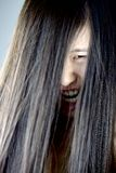 Shouting asian female monster with long hair on face Royalty Free Stock Images