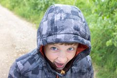 A shouting boy with a hood on his head royalty free stock image