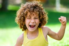 Shouting boy pulling fist up. Close up portrait of boy shouting and showing fist outdoors Royalty Free Stock Photography