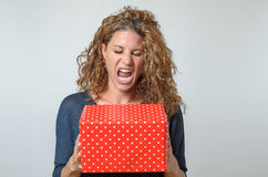 Shouting brunette Woman Holding Red Gift Box Stock Photos