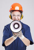 Shouting Caucasian Female Worker Posing with Megaphone and Wearing Hardhat for Protection. Stock Photography