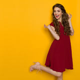 Shouting Elegant Woman In Maroon Dress Is Standing On One Leg Royalty Free Stock Image
