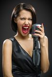 Shouting female musician keeping microphone Royalty Free Stock Photography