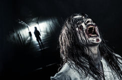 The shouting female zombie. The shouting horror zombie girl in a dark corridor. Halloween Royalty Free Stock Photo
