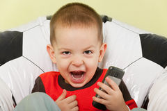 Shouting football fan. A little shouting boy is sitting on the football armchair Stock Photo