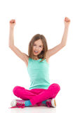 Shouting girl with arms raised. Girl sitting on the floor with arm raised and shouting. Full length studio shot isolated on white Royalty Free Stock Photo