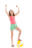 Shouting girl with beach ball looking up. Shouting girl in pink shirt and green shorts posing with a beach ball under her foot. Full length studio shot isolated Royalty Free Stock Image