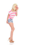 Shouting girl. Beautiful blonde girl in high heels and pink top standing and shouting. Full length studio shot isolated on white Stock Photos
