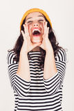 Shouting girl. Beautiful and funny girl with striped dress and yellow wool cap shouting hands next to her mouth. Focus on mouth Stock Images
