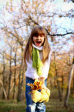 Shouting girl with leaves and teddy bear Royalty Free Stock Photography