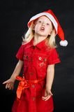Shouting girl in red dress and santa hat Stock Photos