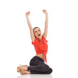 Shouting girl sitting with arms raised Royalty Free Stock Photo