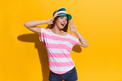 Shouting Girl In Sun Visor Cap. Shouting young woman in pink stripped shirt and blue sun visor posing and holding head in hands. Waist up studio shot on yellow Royalty Free Stock Image