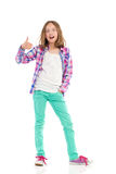 Shouting girl with thumb up. Young girl in lumberjack shirt and green trousers showing thumb up and shouting. Full length studio shot isolated on white Royalty Free Stock Photography
