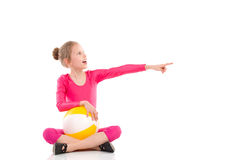 Shouting gymnastics girl with a ball pointing. Shouting girl sitting on the floor with legs crossed, holding a ball on her knees, looking away and pointing Stock Images