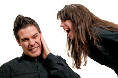 Shouting in his ear. Girl shouting in guy's ear isolated on white background Stock Images