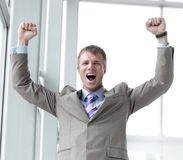 Shouting with joyful young entrepreneur raised hands. Stock Photos
