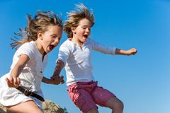 Shouting kids having fun jumping. Two kids shouting and jumping together outdoors Royalty Free Stock Image