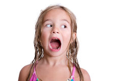Shouting little girl with wet hair. Close up on shouting little blond girl with wet hair from swimming looking sideways over white background Stock Photo